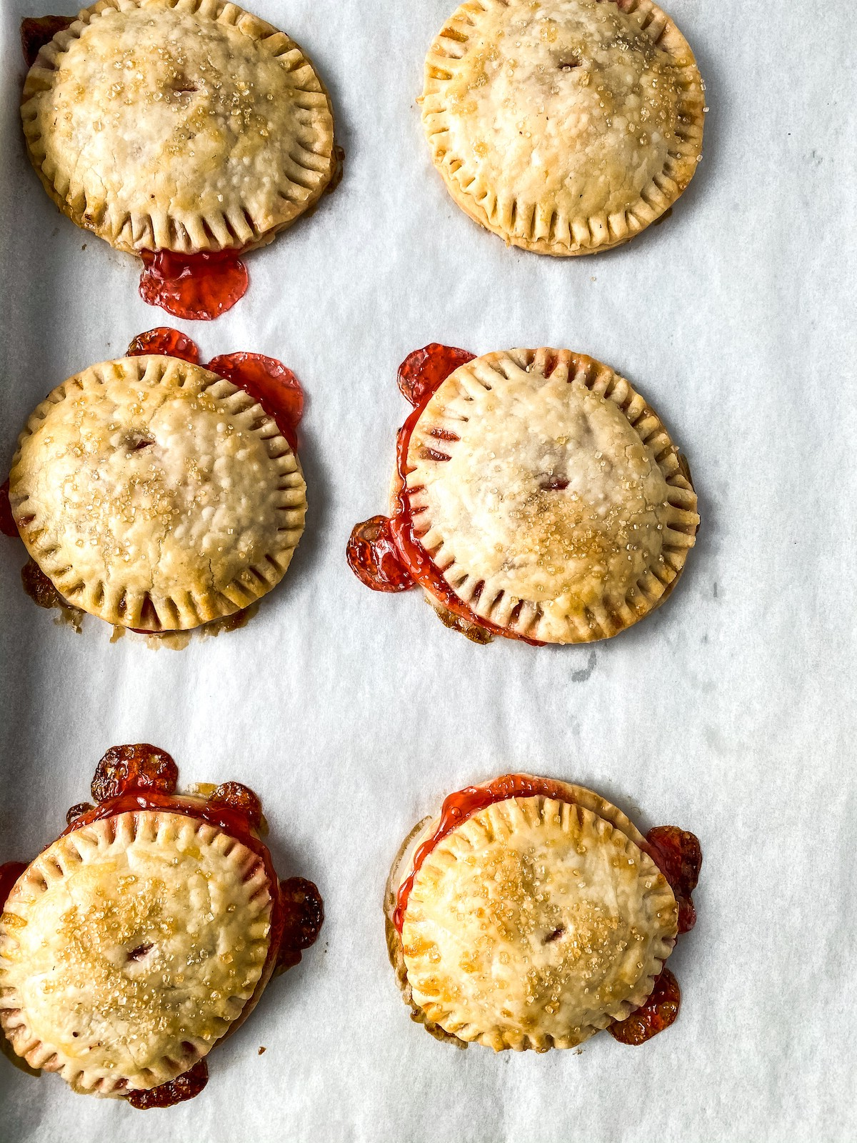 Baked strawberry hand pies on baking sheet