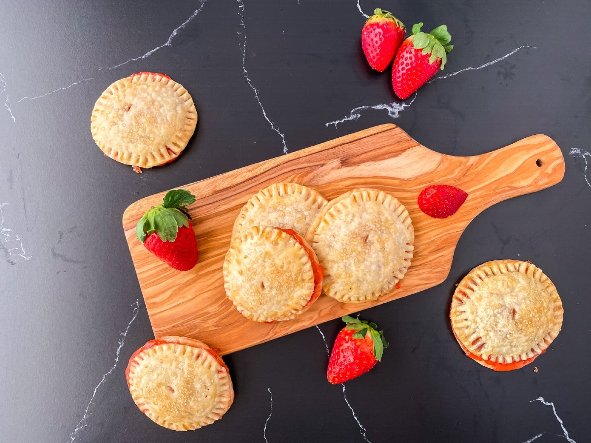 Strawberry hand pies on wooden cutting board