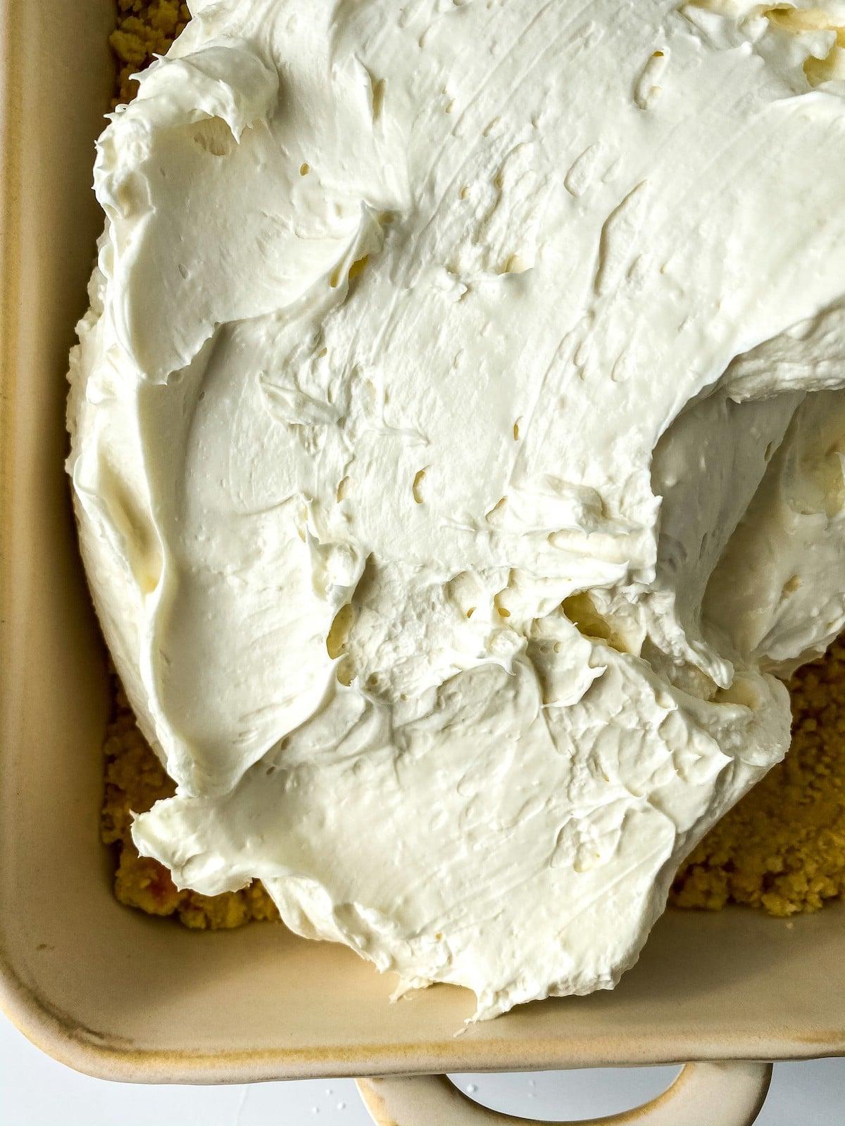 Spreading cream cheese into baking dish