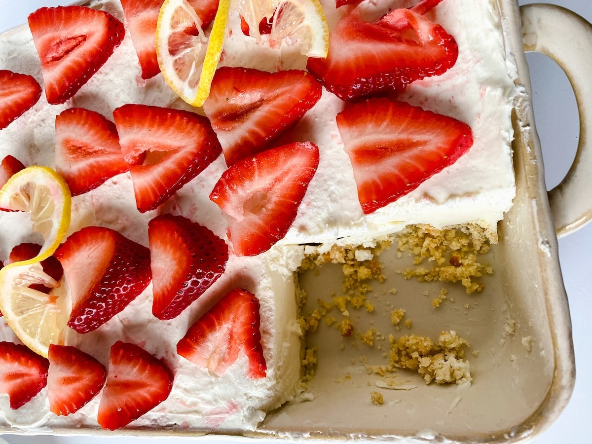 Lemon cheesecake with strawberry and lemon slices on top and slice out