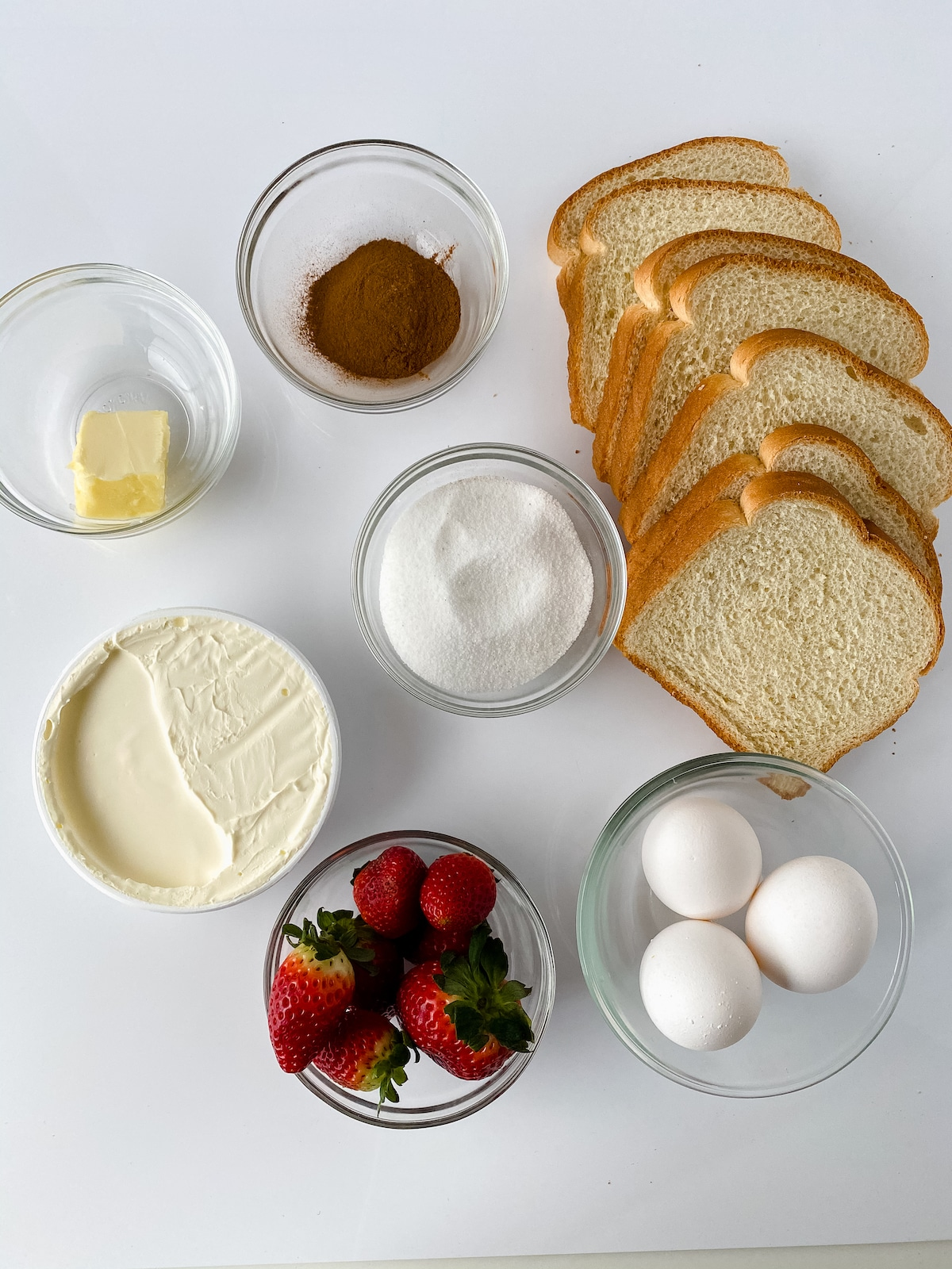Ingredients for Strawberry stuffed French toast in glass bowls on white surface