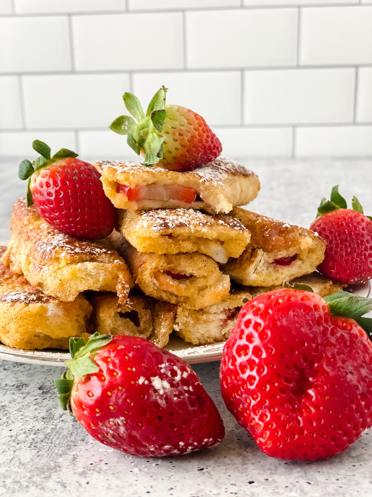 Stack of strawberry french toast on white plate with berries in front of plate