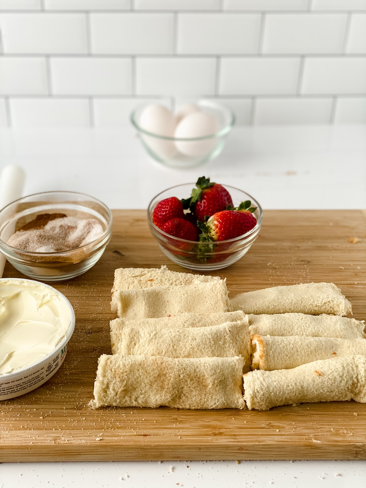 Bread folded into rolls by bowl of strawberries on cutting board