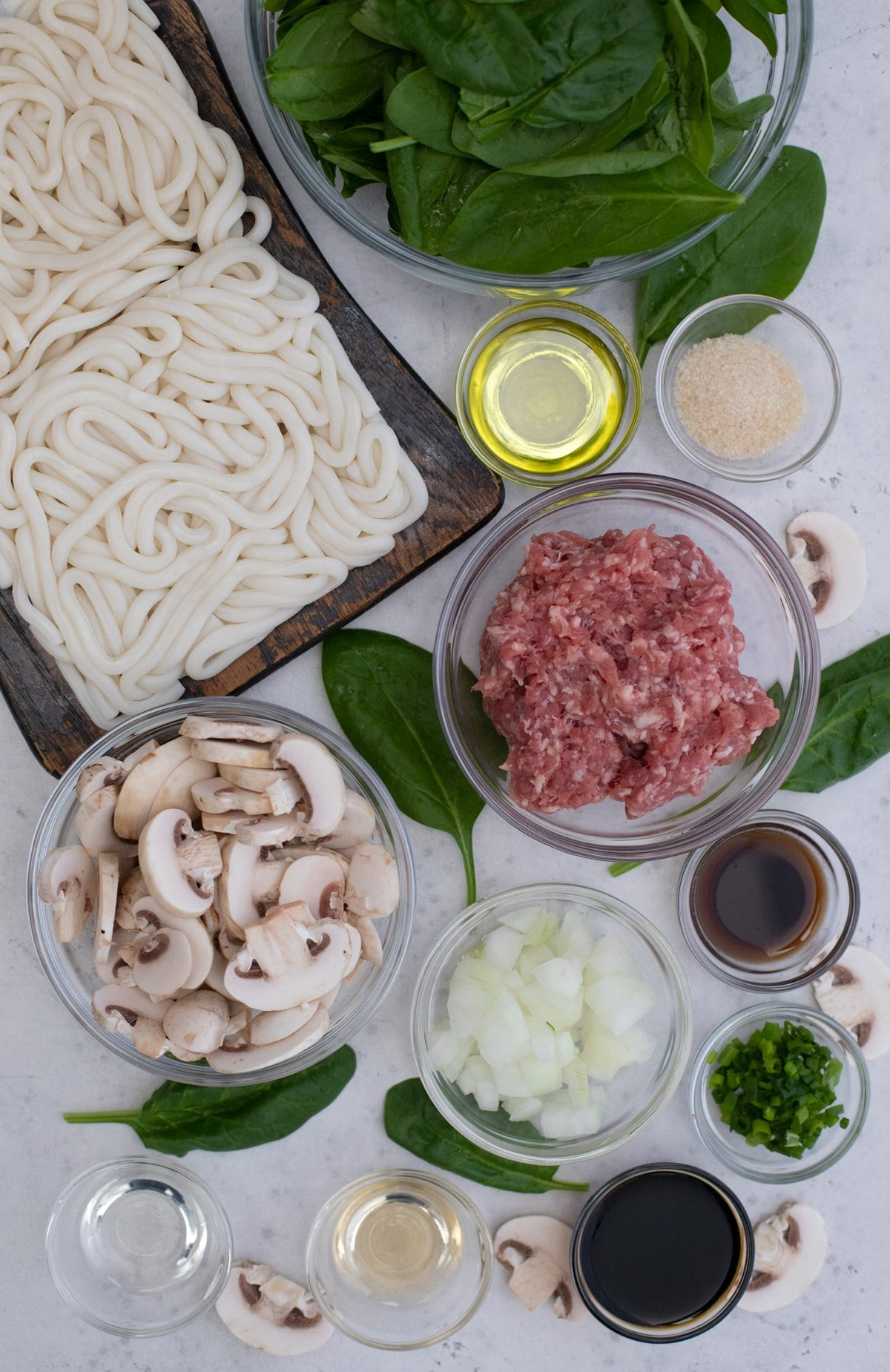 Ingredients for udon noodle stir fry on white table