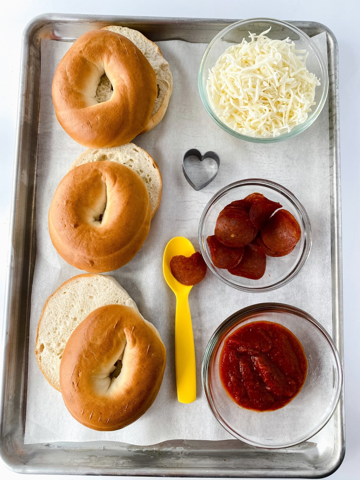 Ingredients for pizza bagels on baking sheet
