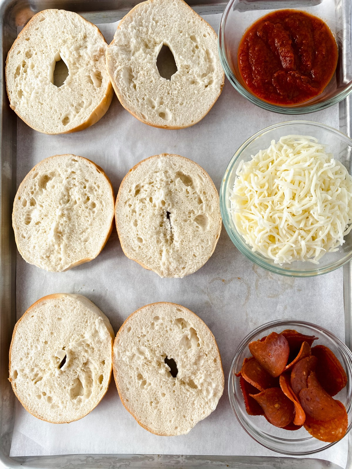 Halved bagels on tray with bowls of sauce and toppings