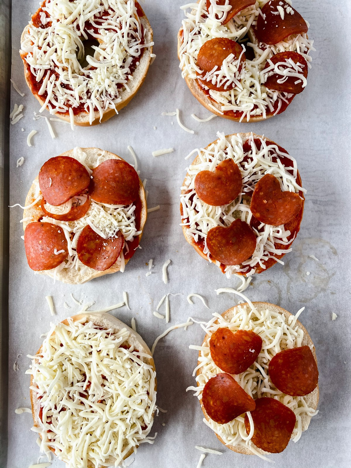 Pizza bagels topped with cheese and pepperoni unbaked