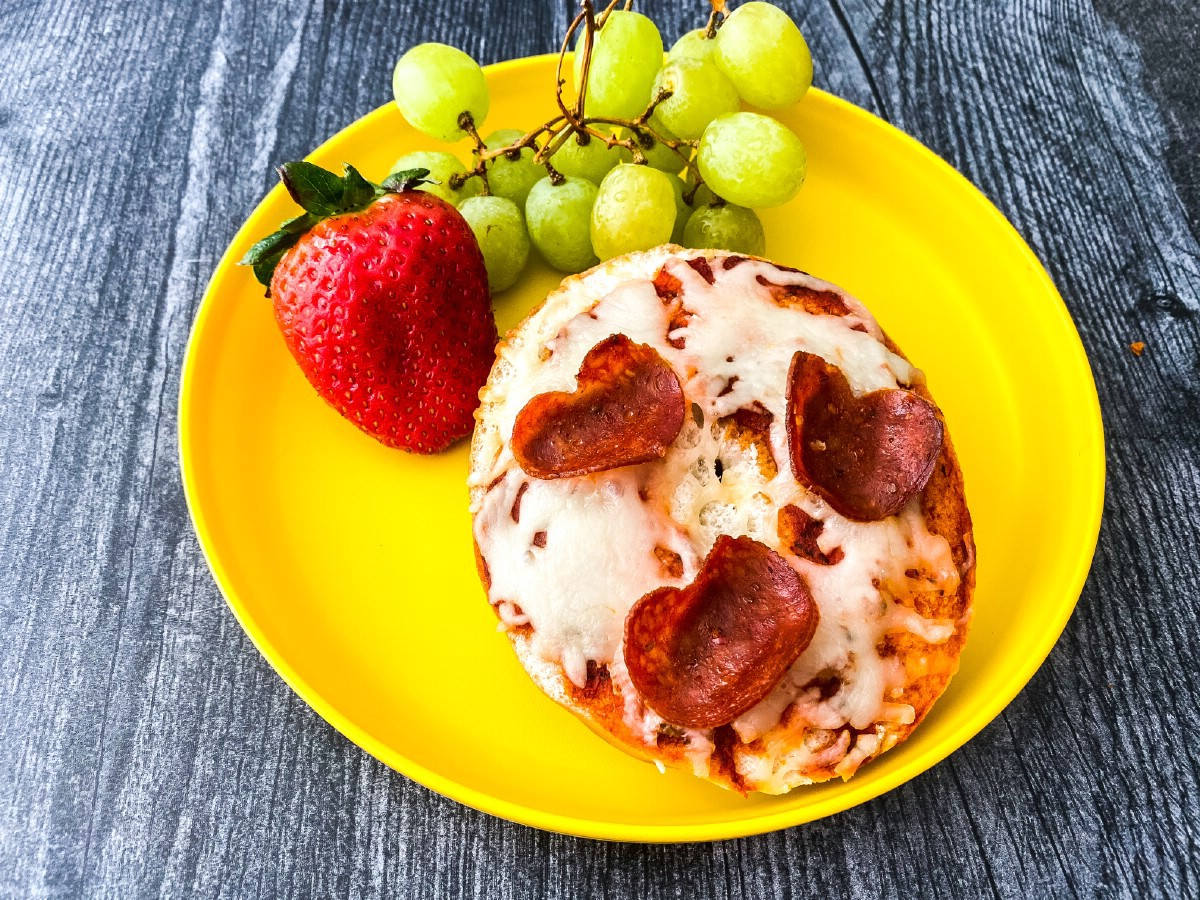 Pepperoni bagel pizza on yellow plate