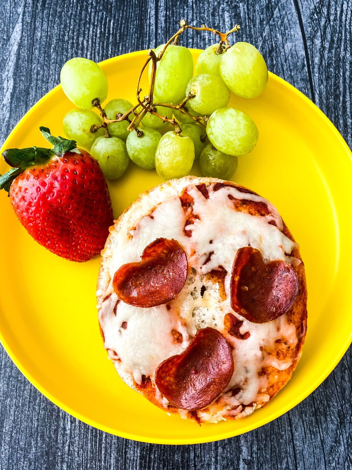 Yellow plate with mini pizza and fruit