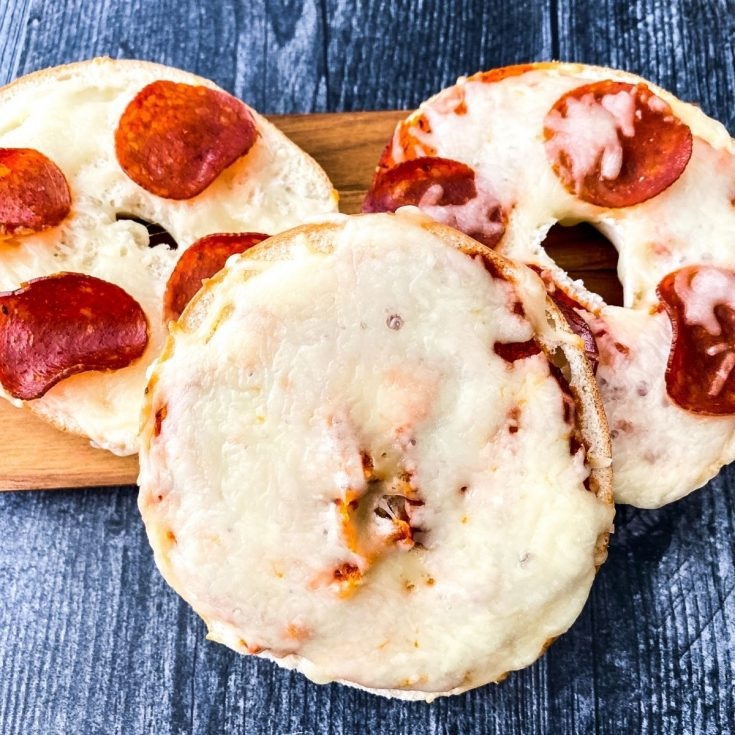 Pepperoni and cheese bagel pizzas on cutting board