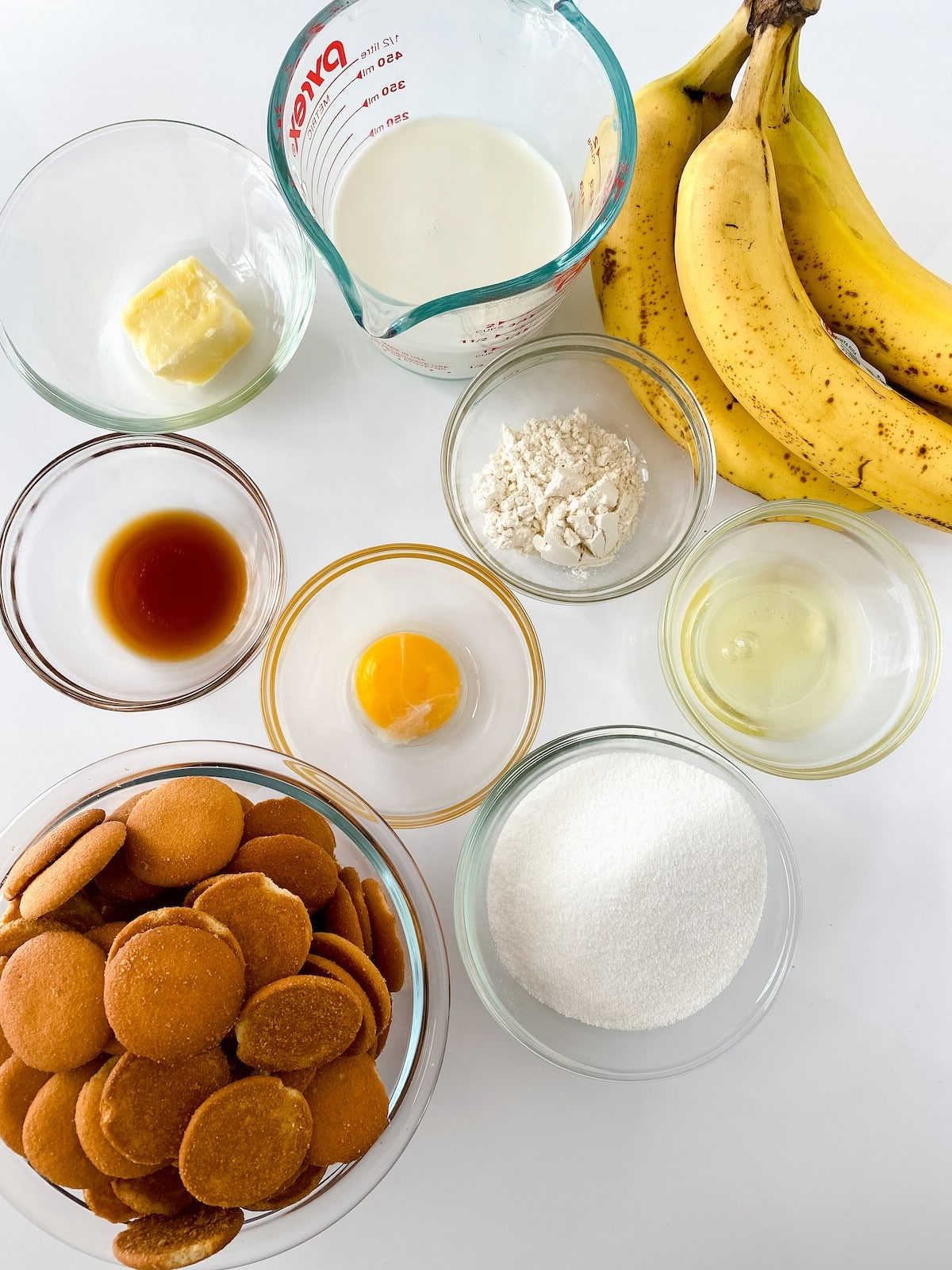 Ingredients for banana pudding in glass bowls on white table