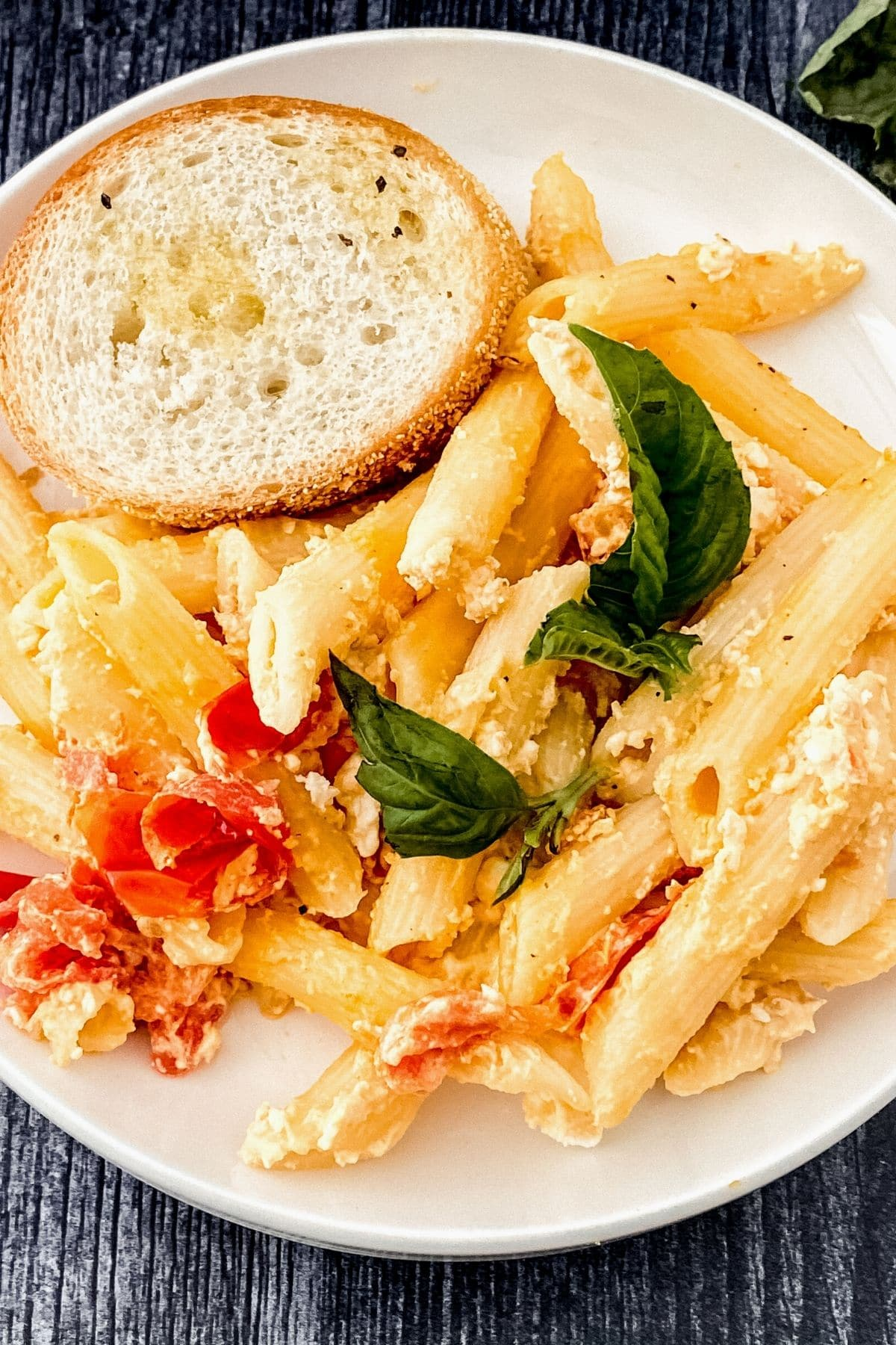 Baked feta pasta in white bowl with bread