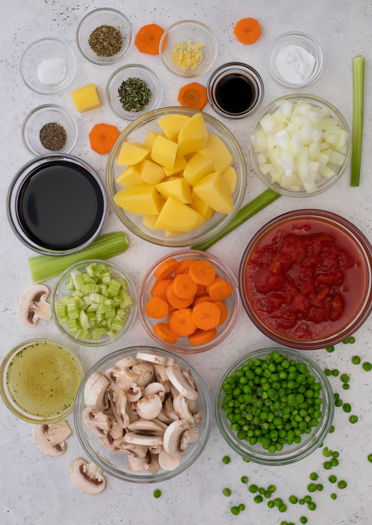 Ingredients for vegetable soup in glass bowls on white table