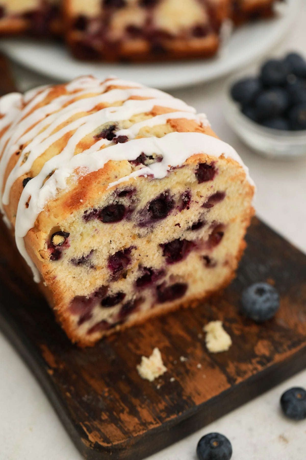 Loaf of blueberry bread with end cut off on cutting board