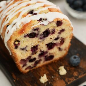 Loaf of sweet bread on dark wood cutting board