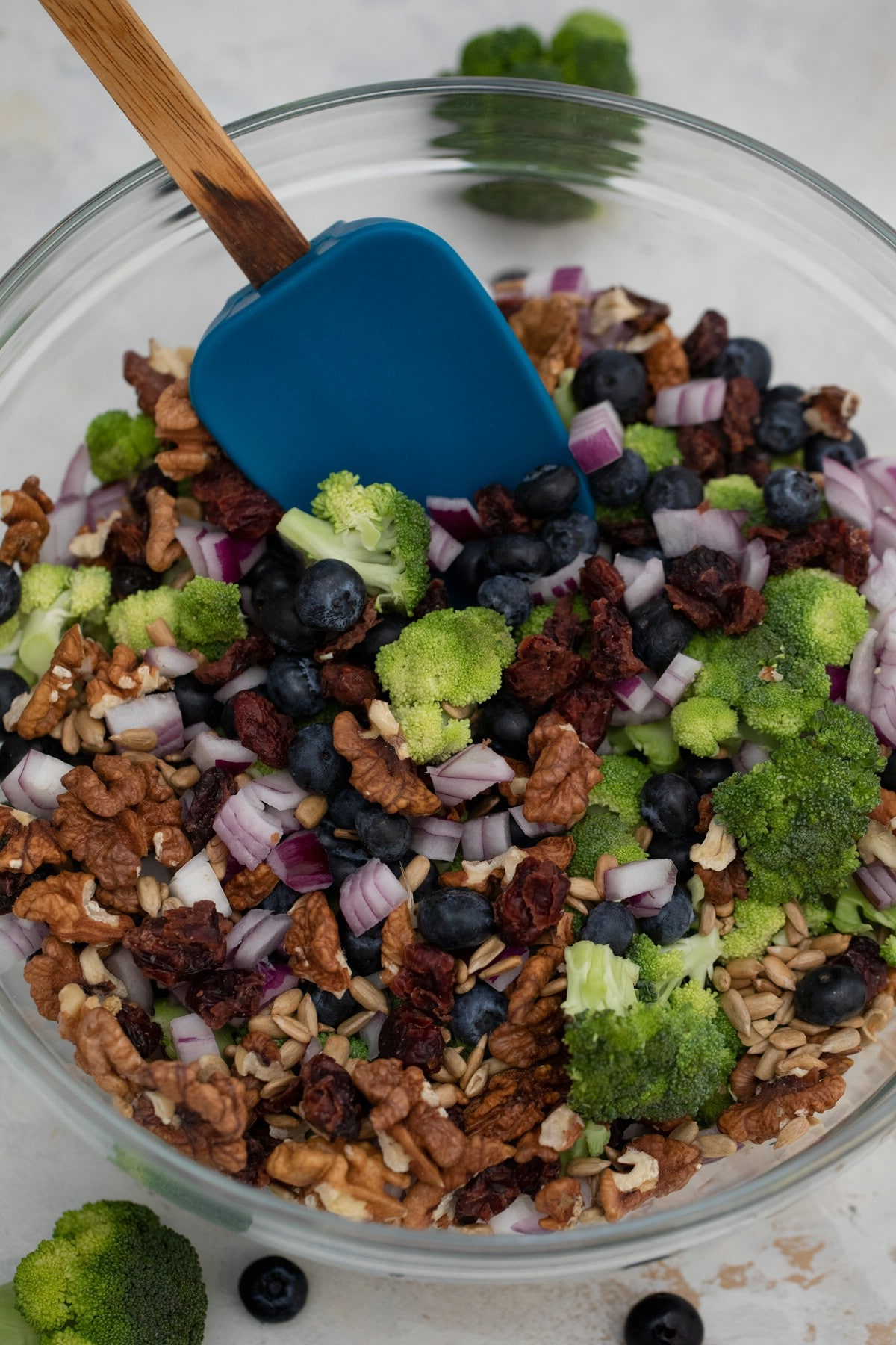 Stirring broccoli with berries and nuts