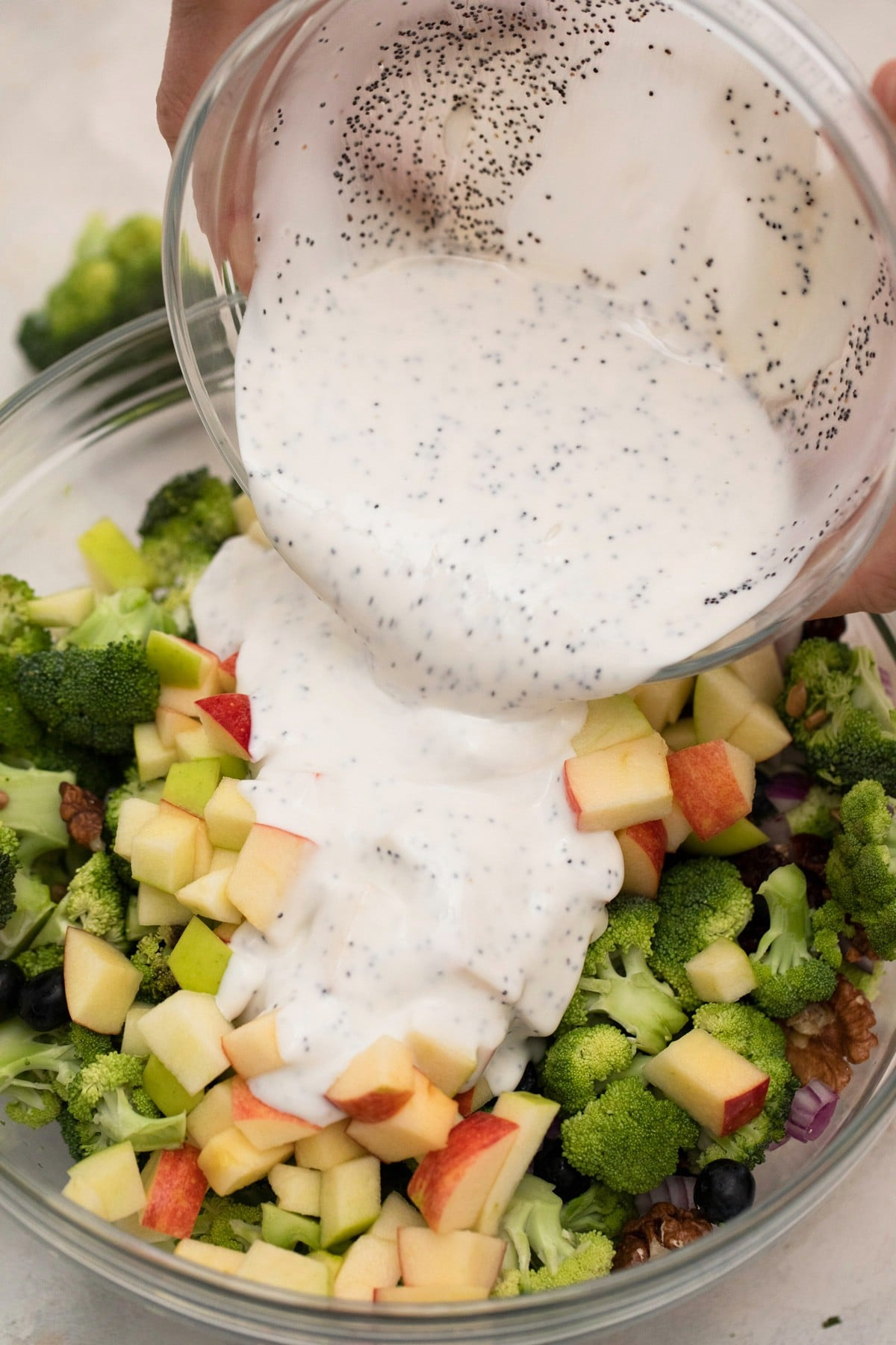 Pouring dressing over broccoli salad