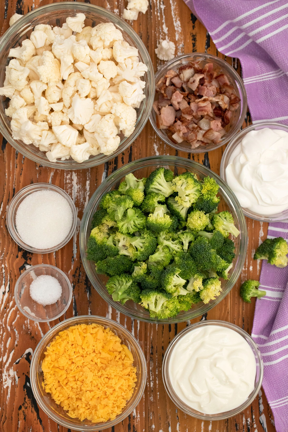 Ingredients for cauliflower and broccoli salad in bowls on table