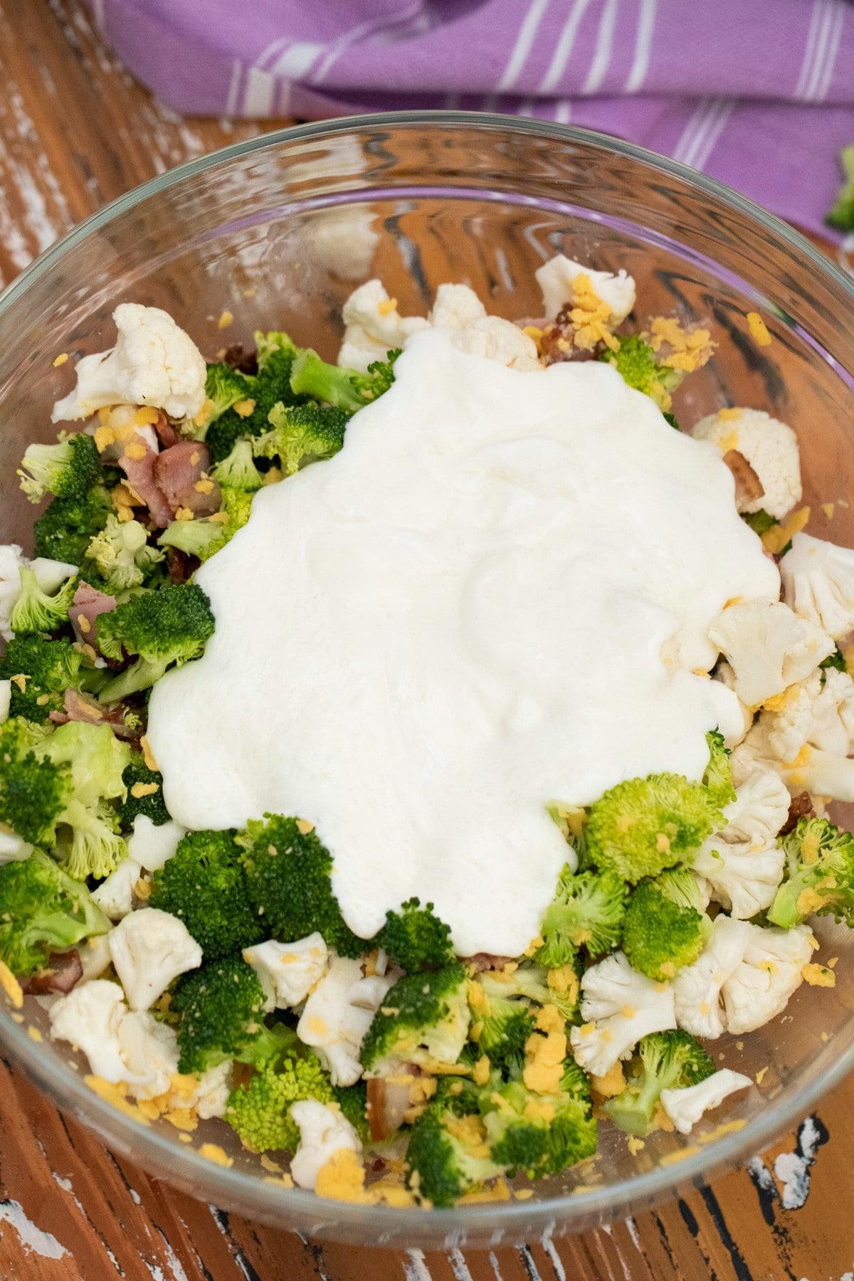 Dressing on top of broccoli cauliflower salad