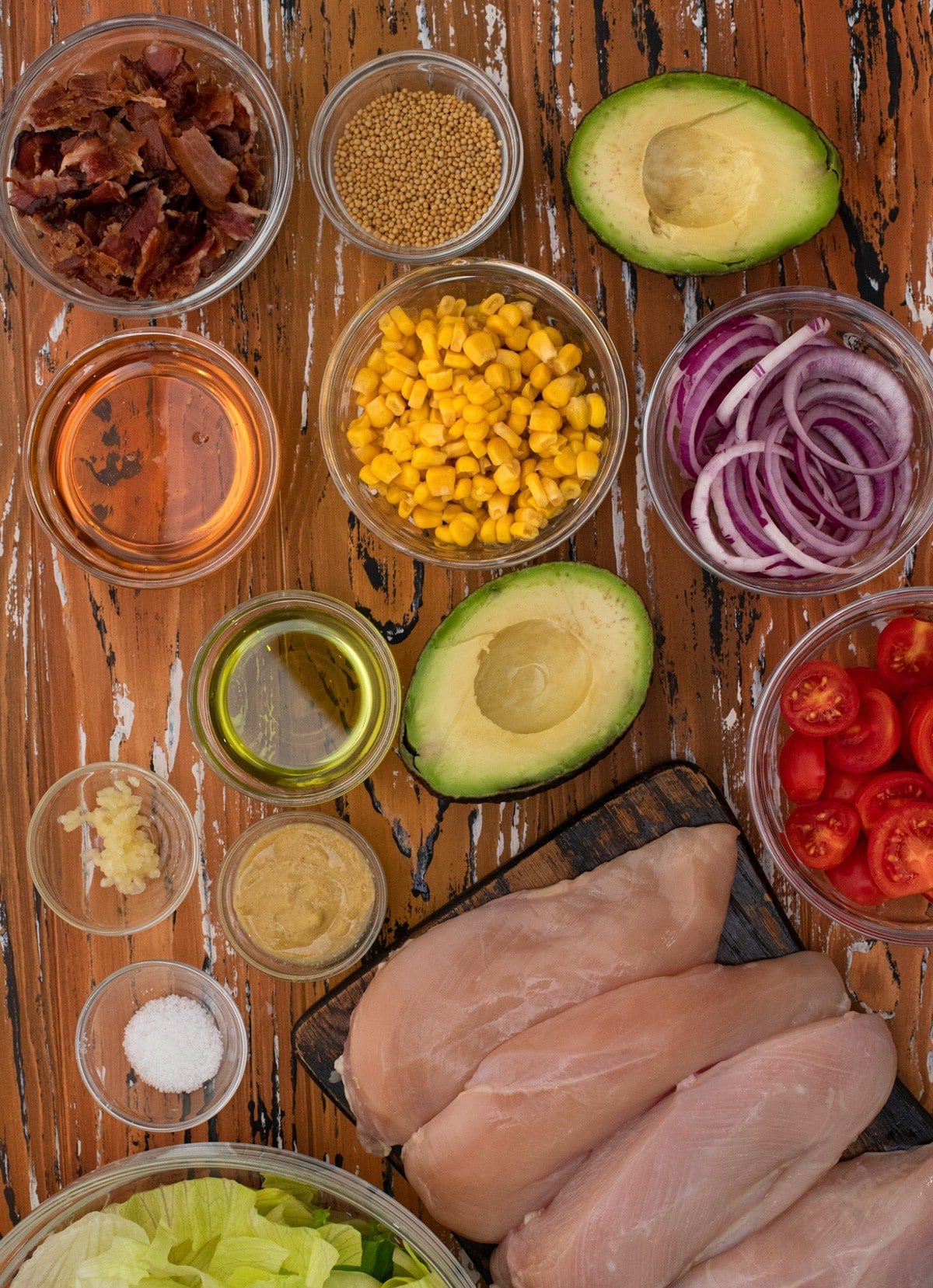 Ingredients for chicken salad in glass bowls on cutting board