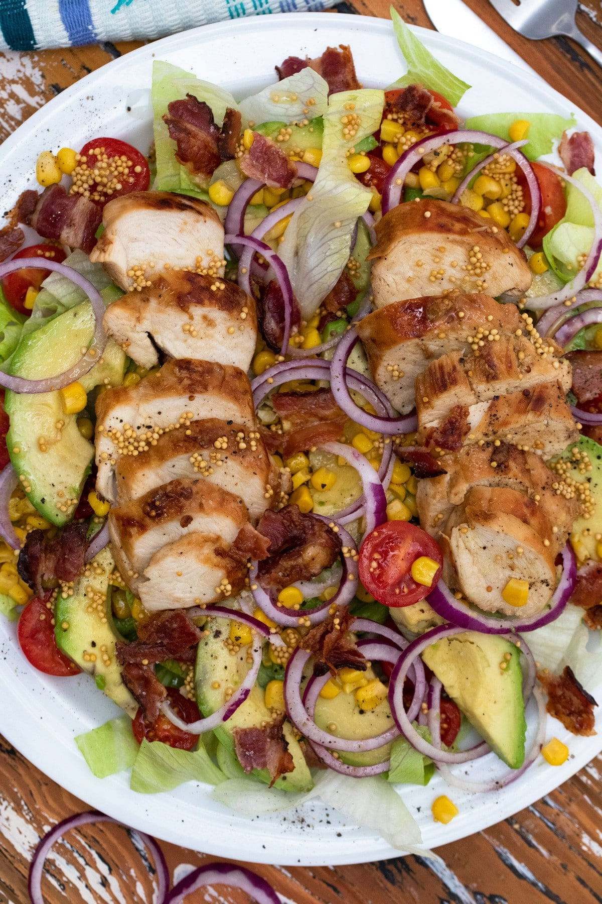 White plate topped with salad featuring avocado and grilled chicken