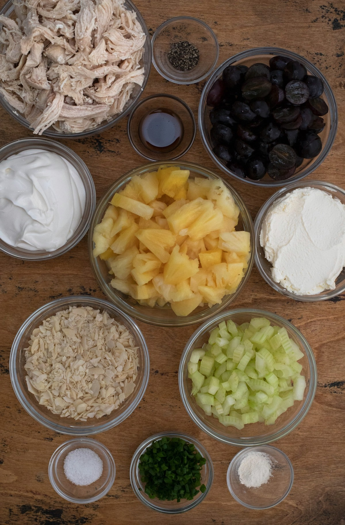 Ingredients for chicken salad in clear bowls on wooden table