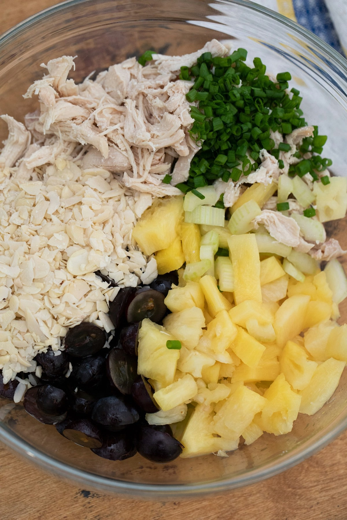 Large glass bowl filled with chicken, grapes, pineapple, and onions