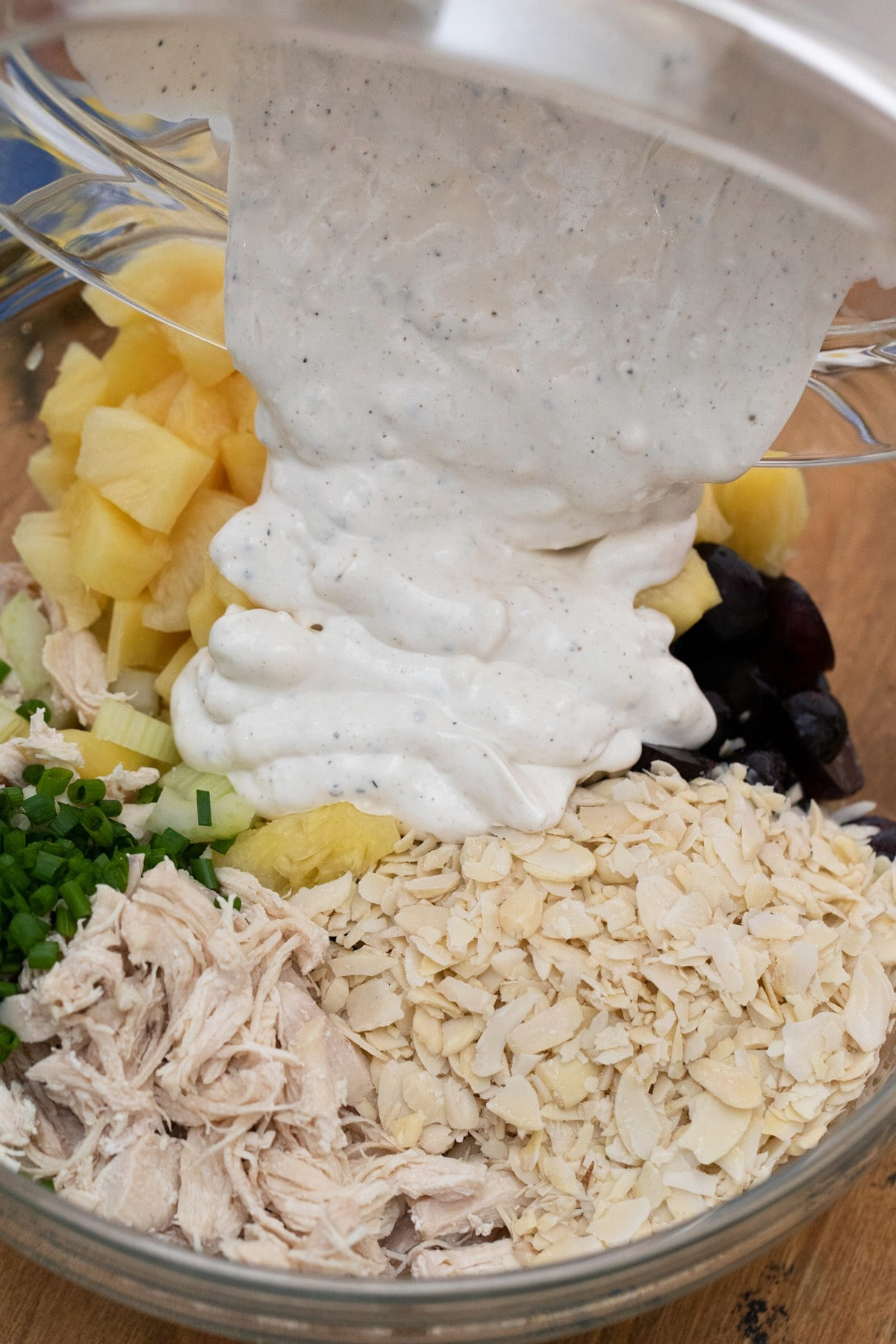 Pouring dressing over bowl of chicken and fruit