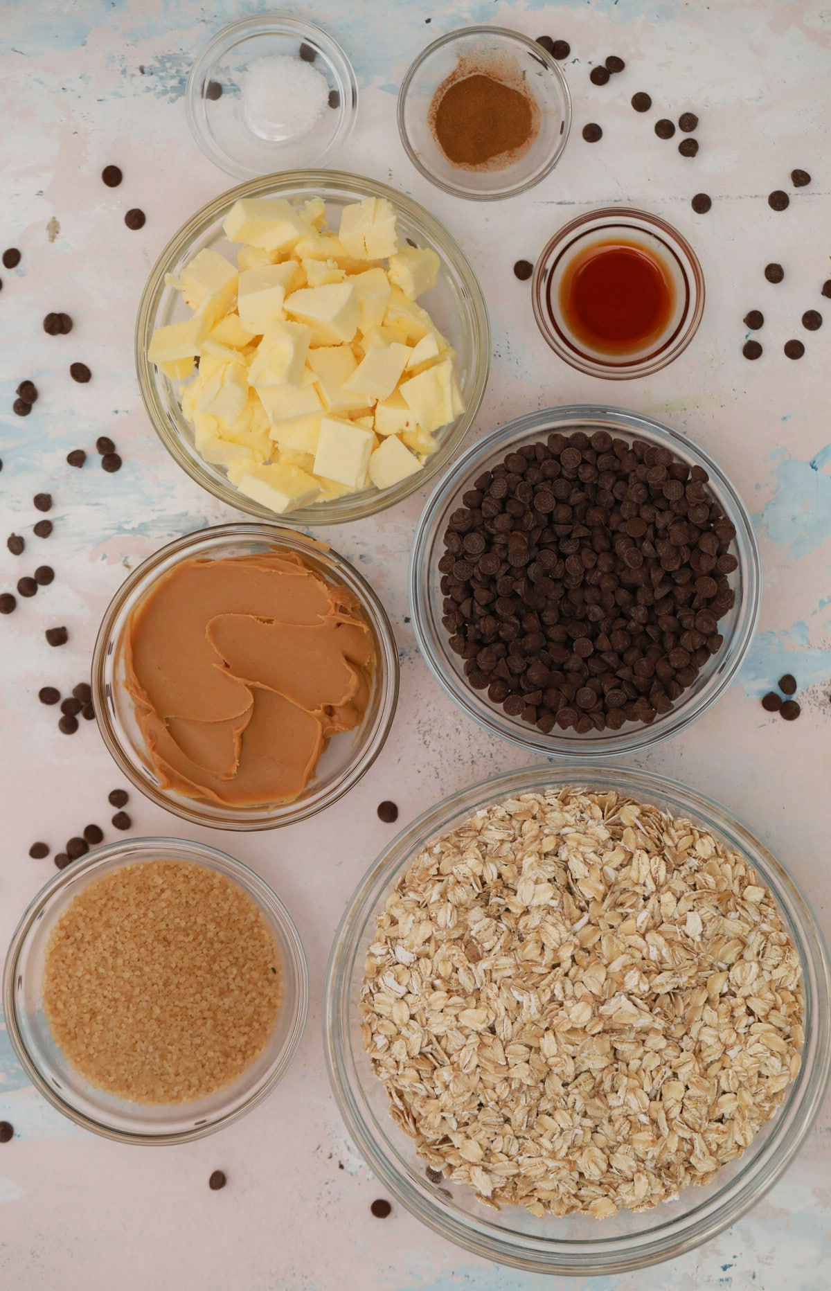 Ingredients for oatmeal bars in glass bowls on white counter