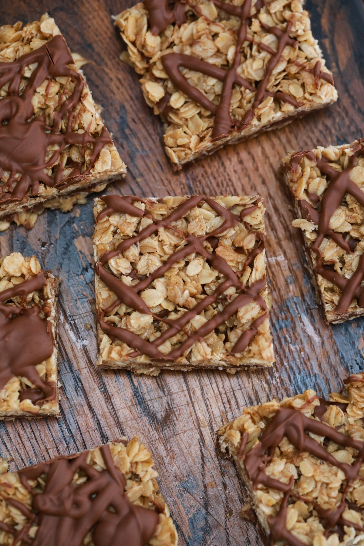 Oatmeal bars with chocolate peanut butter drizzle on wooden table