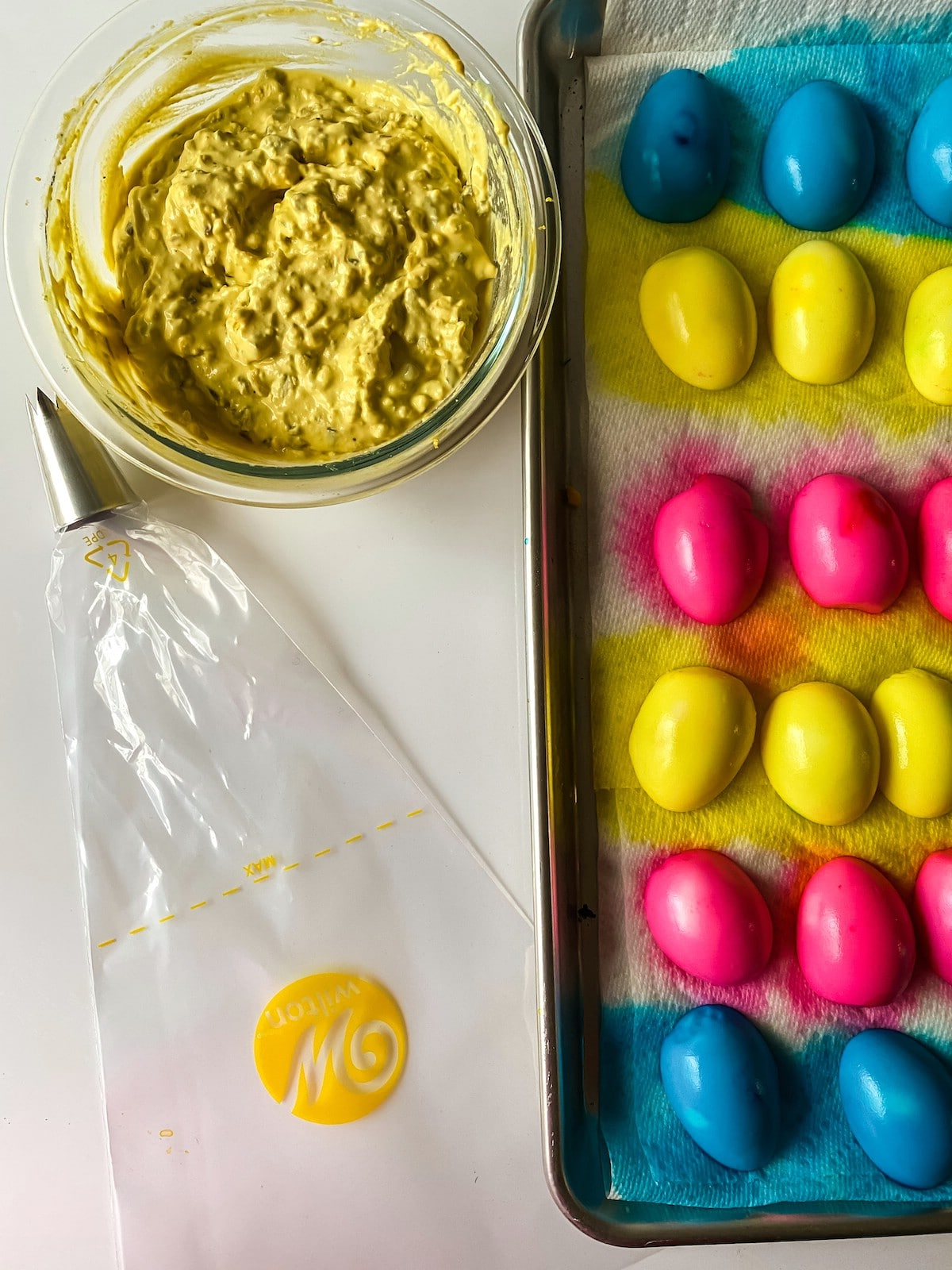Sheet pan with dyed eggs beside bowl of deviled egg filling