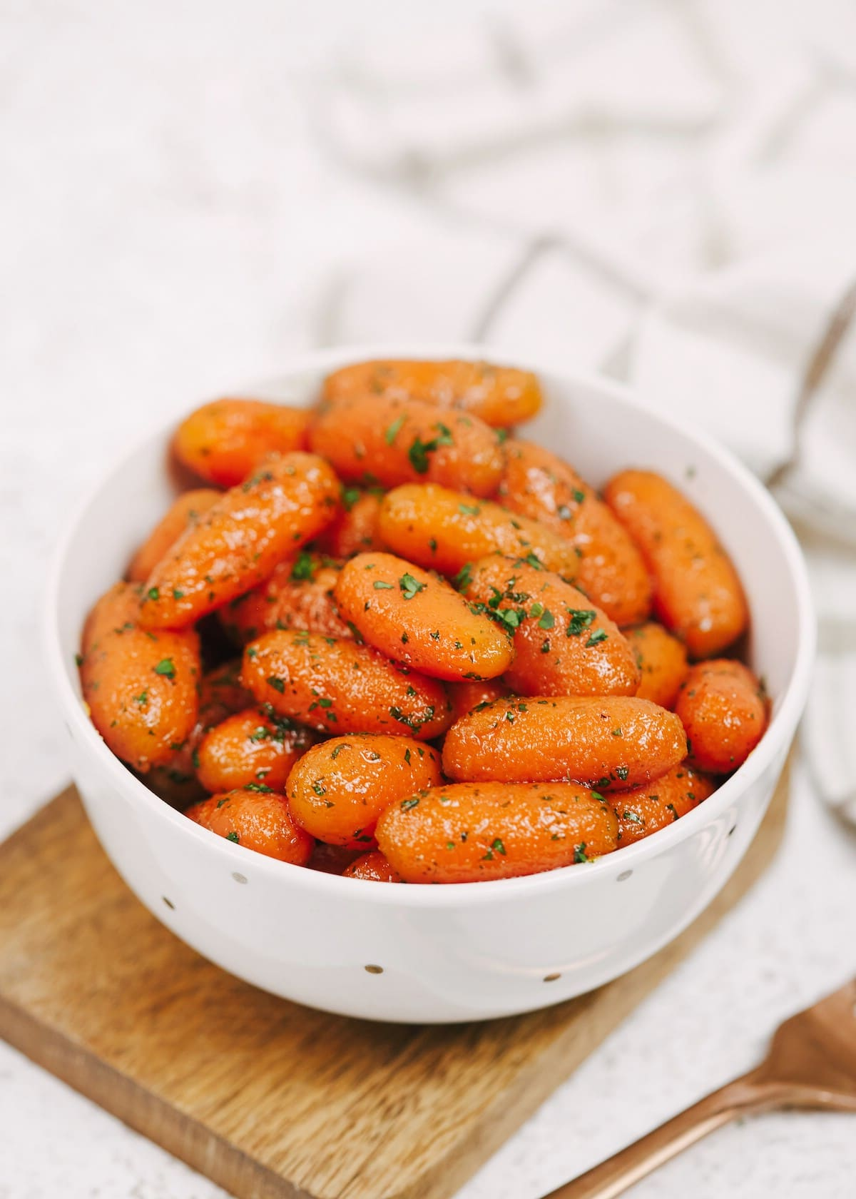 Bowl of candied carrots with parsley on top