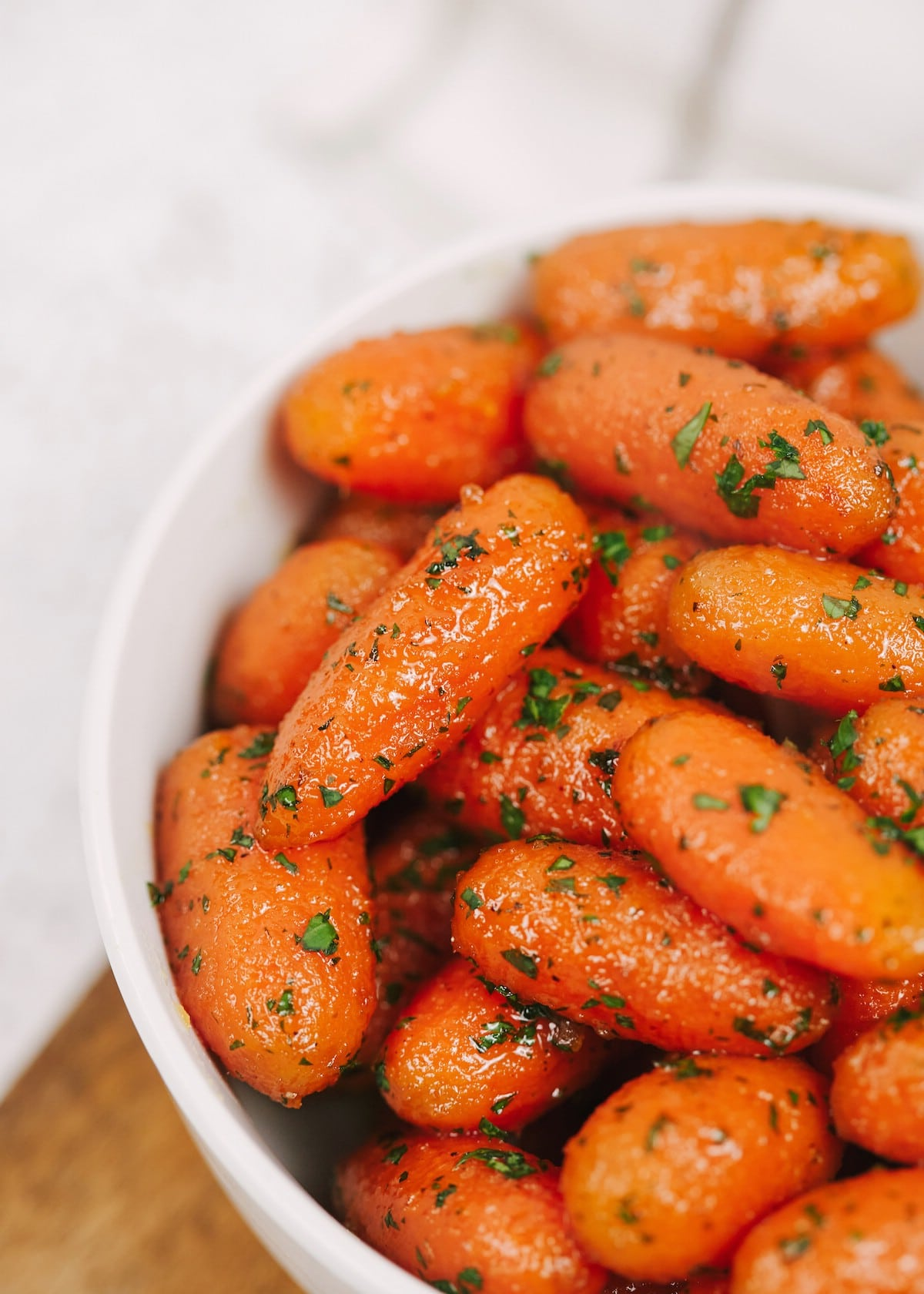 Carrots in white bowl topped with parsley