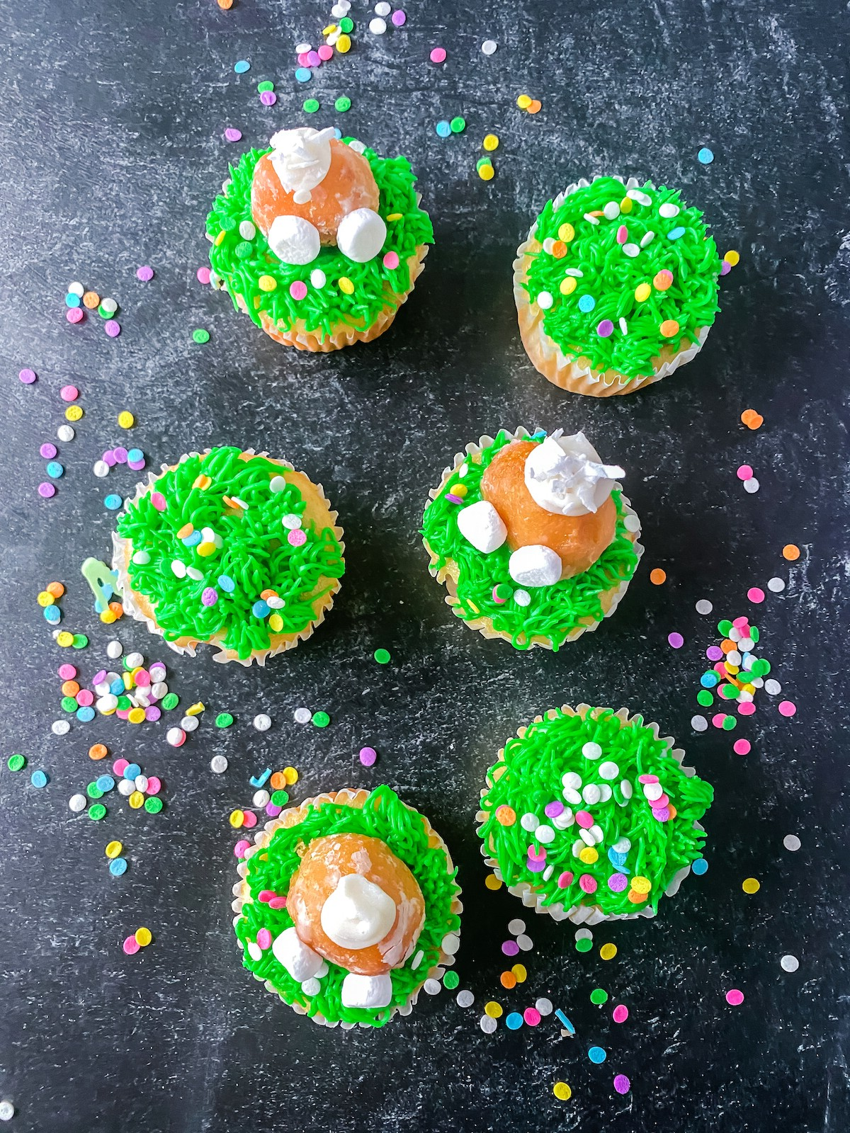 Easter cupcakes with green icing sitting on black surface