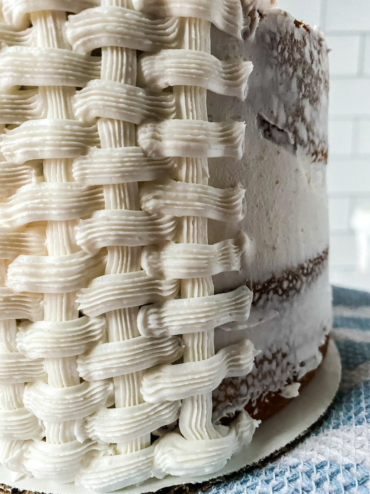 Stripes of white icing in a basket woven design on layer cake