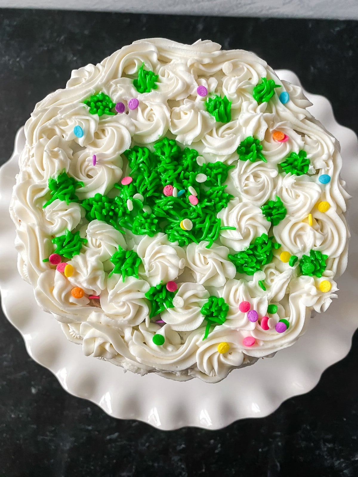 Top of iced cake with white basket weave and green fake grass top