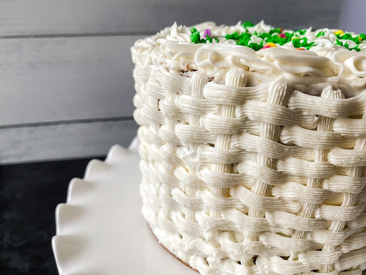 Basket weave white cake on stand in front of wood wall