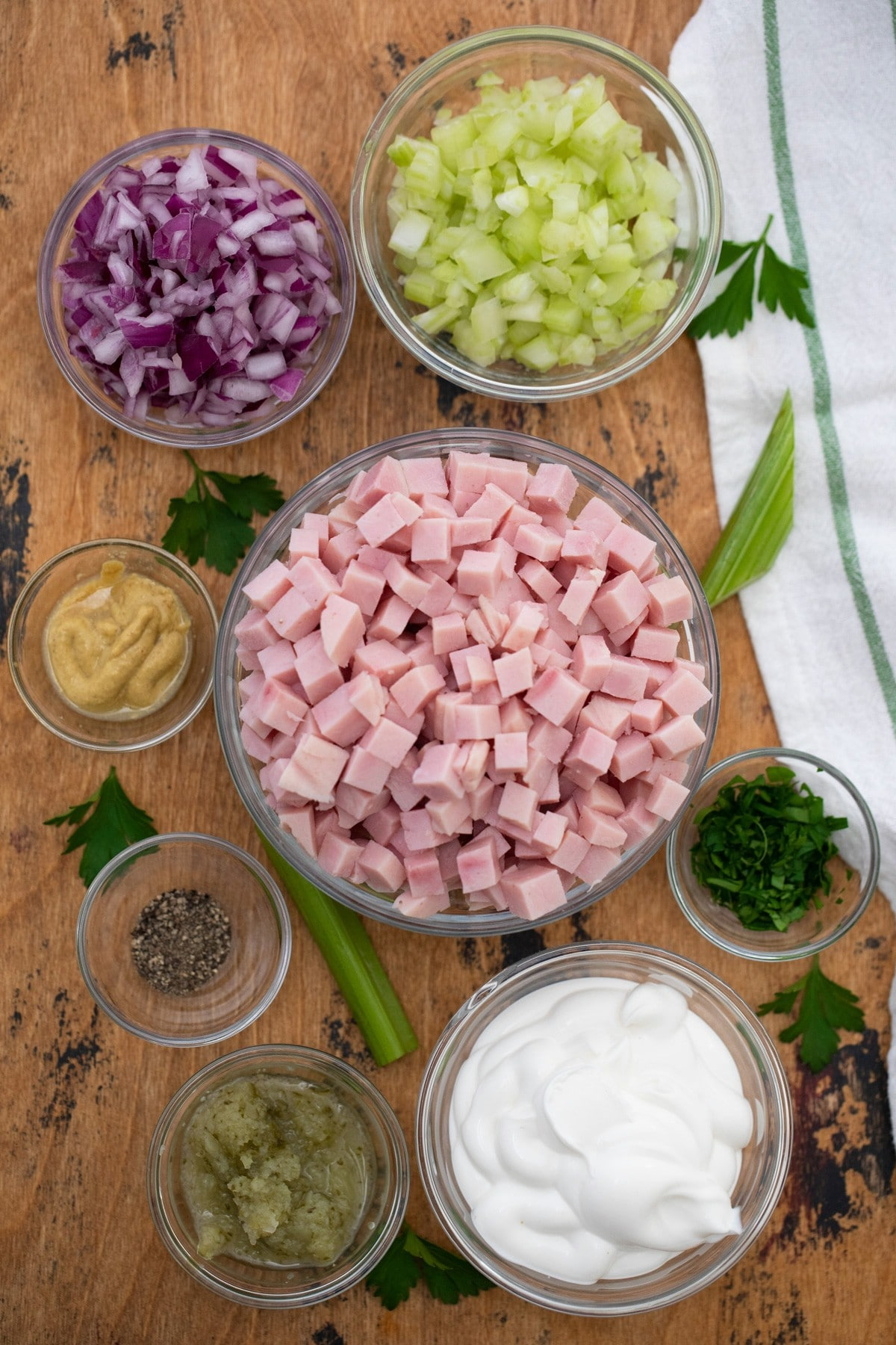 Ingredients for ham salad in bowls on cutting board