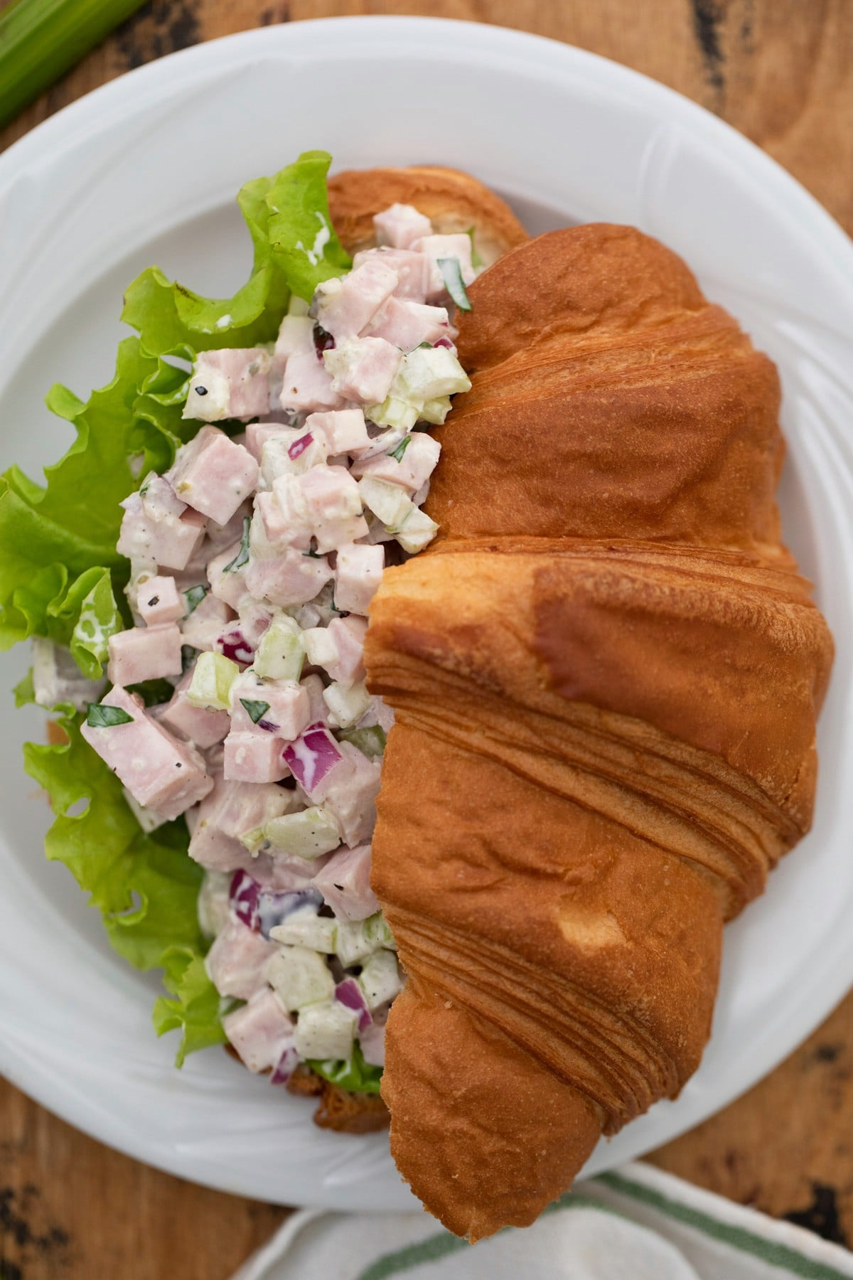 Crossiant with ham salad and lettuce on white plate