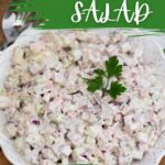White bowl filled with ham salad topped with parsley