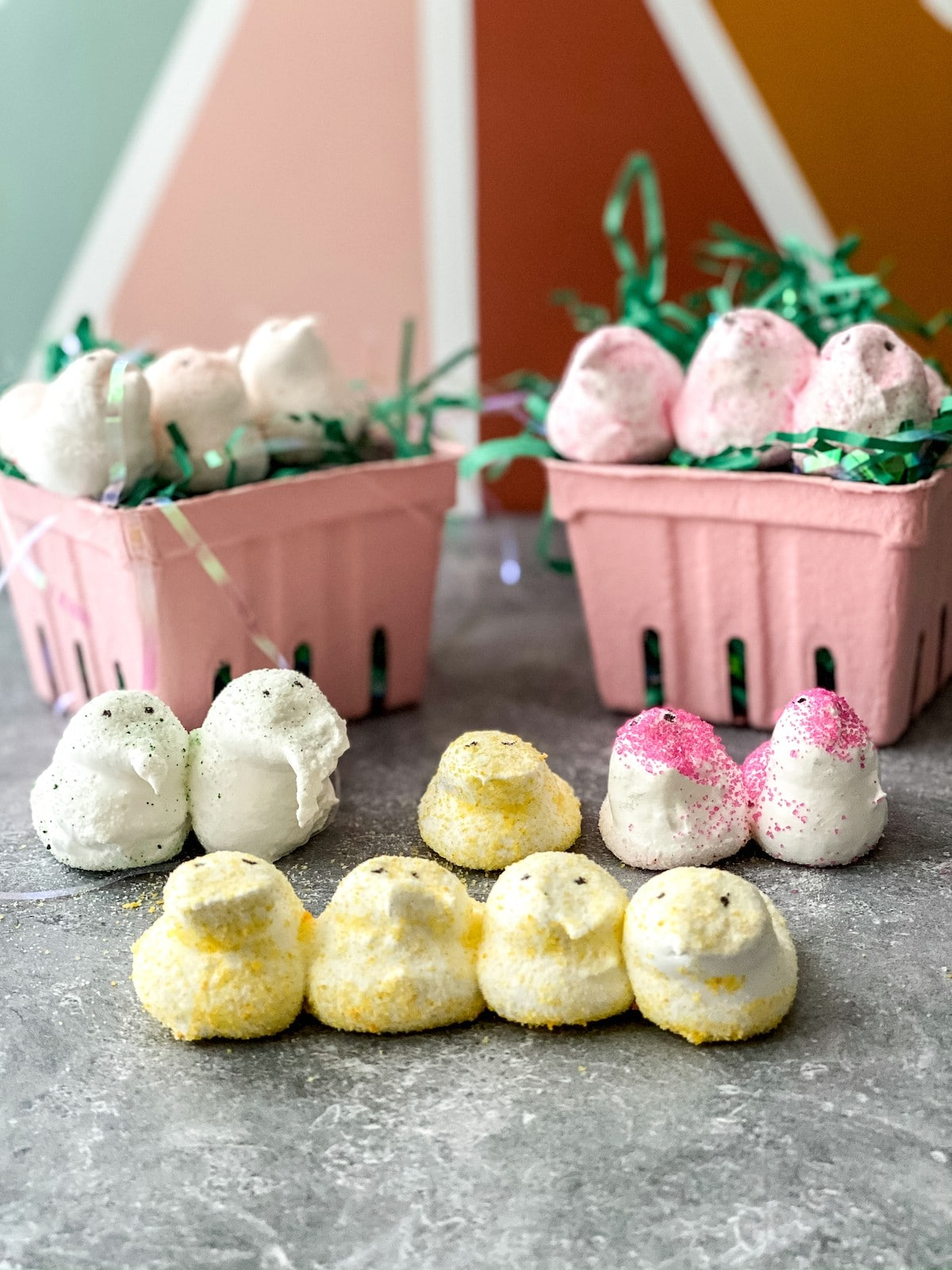 Two pink baskets with fake grass holding pink marshmallow chicks