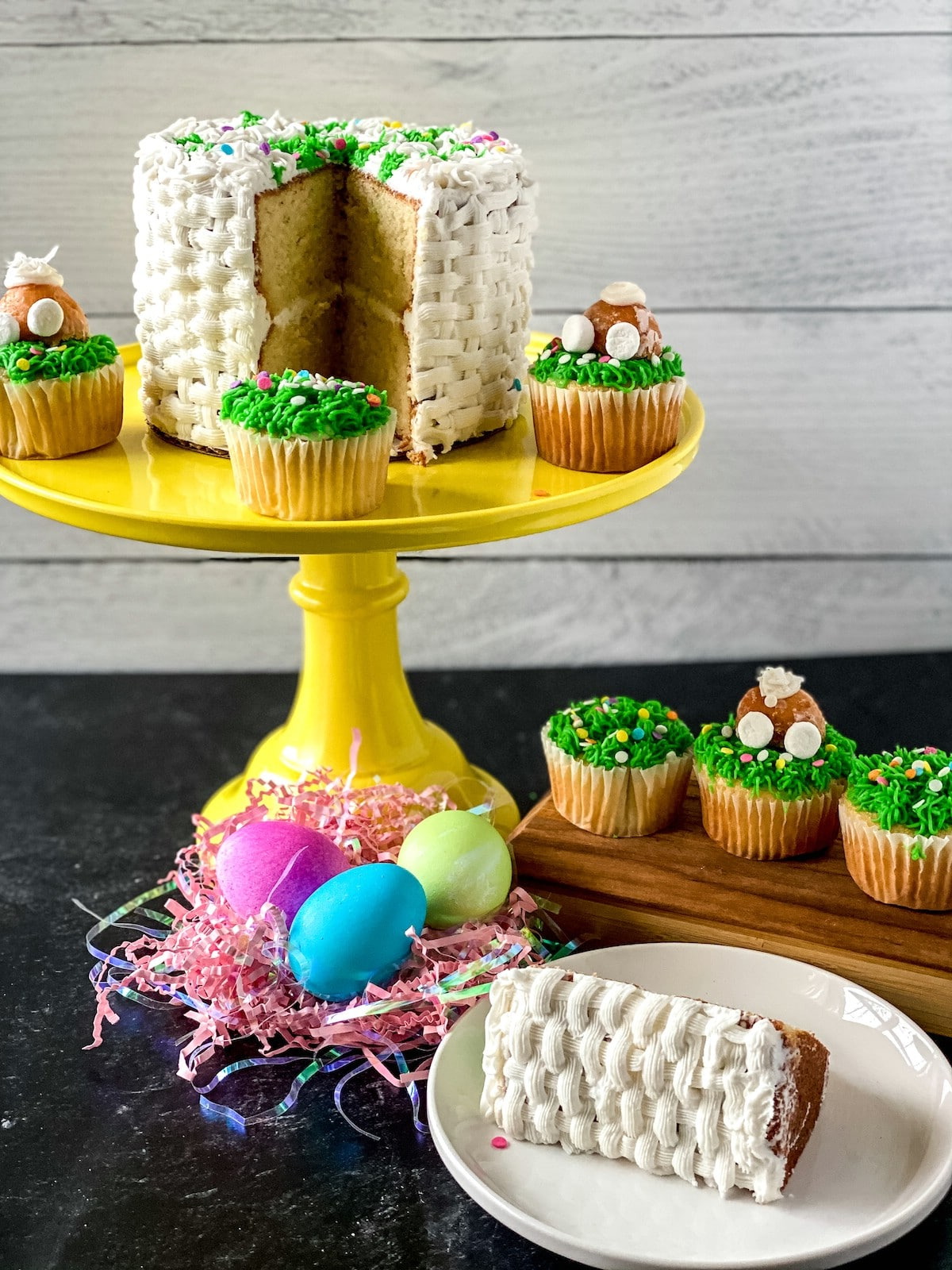 Easter cake on yellow cake stand with slice on white plate