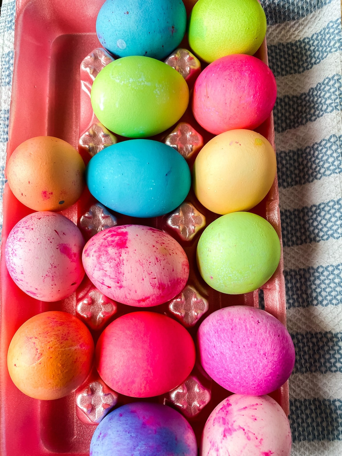 Pink egg carton filled with dyed eggs