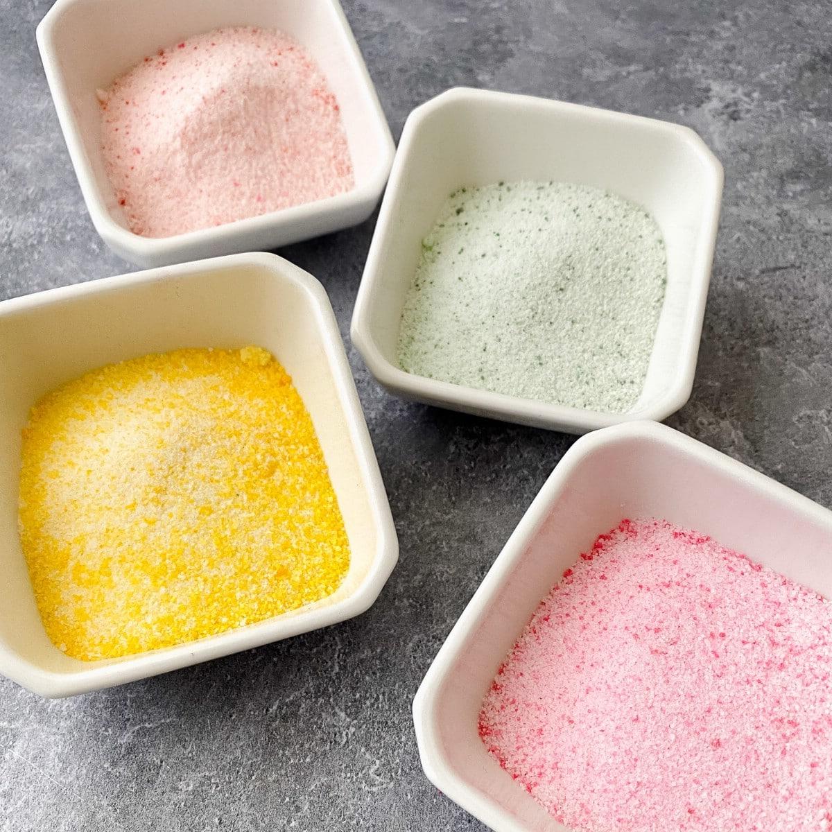 Pastel sanding sugar in white bowls