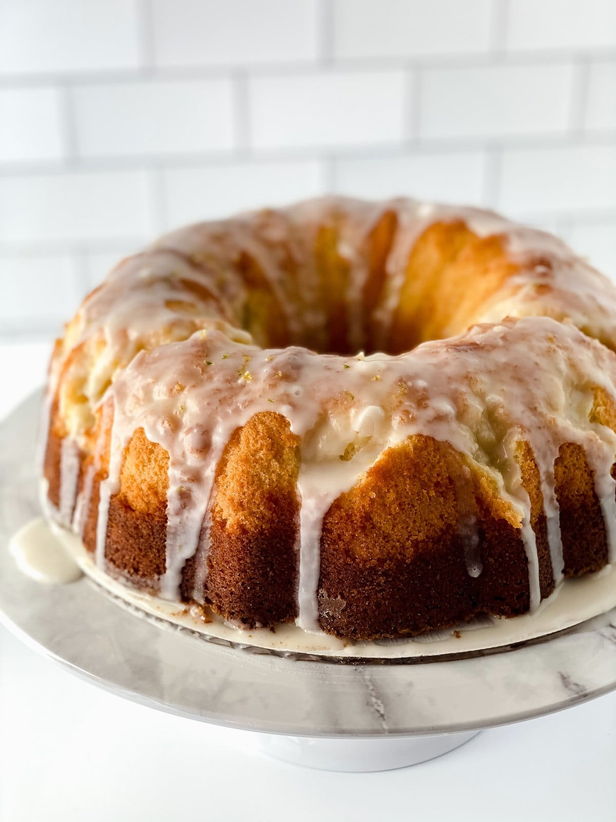 Bundt cake on white cake stand covered with glaze