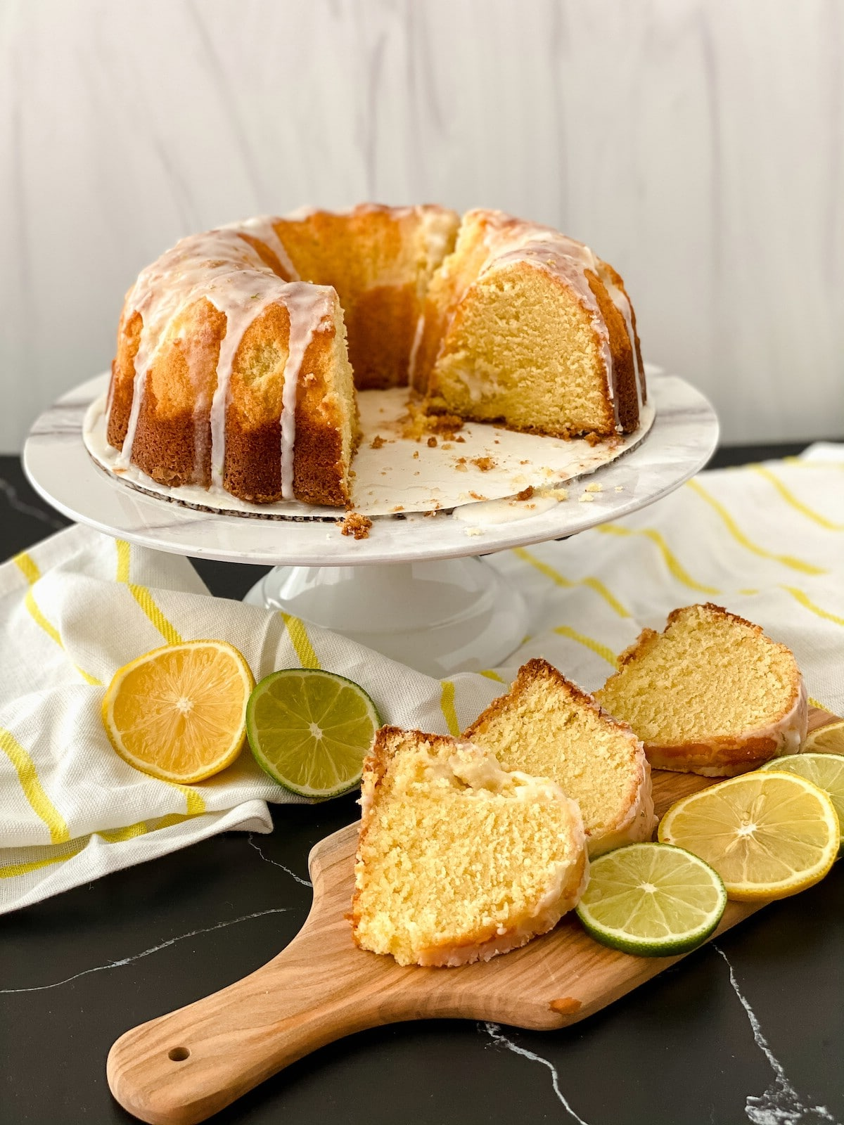 Bundt cake on white cake stand with glaze and slice cut out