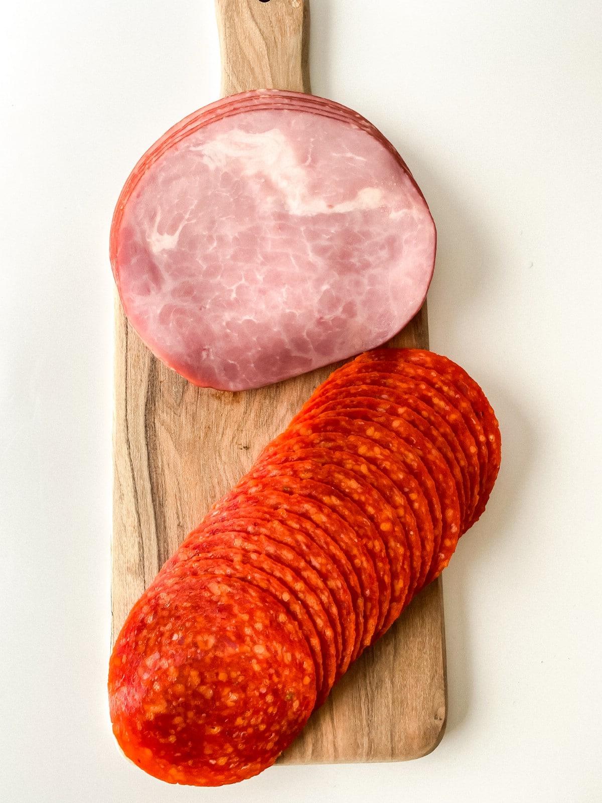 Sliced ham and sliced pepperoni on cutting board