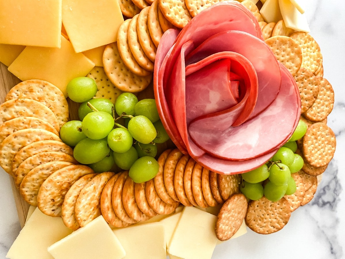 Flower made from ham next to grapes and crackers
