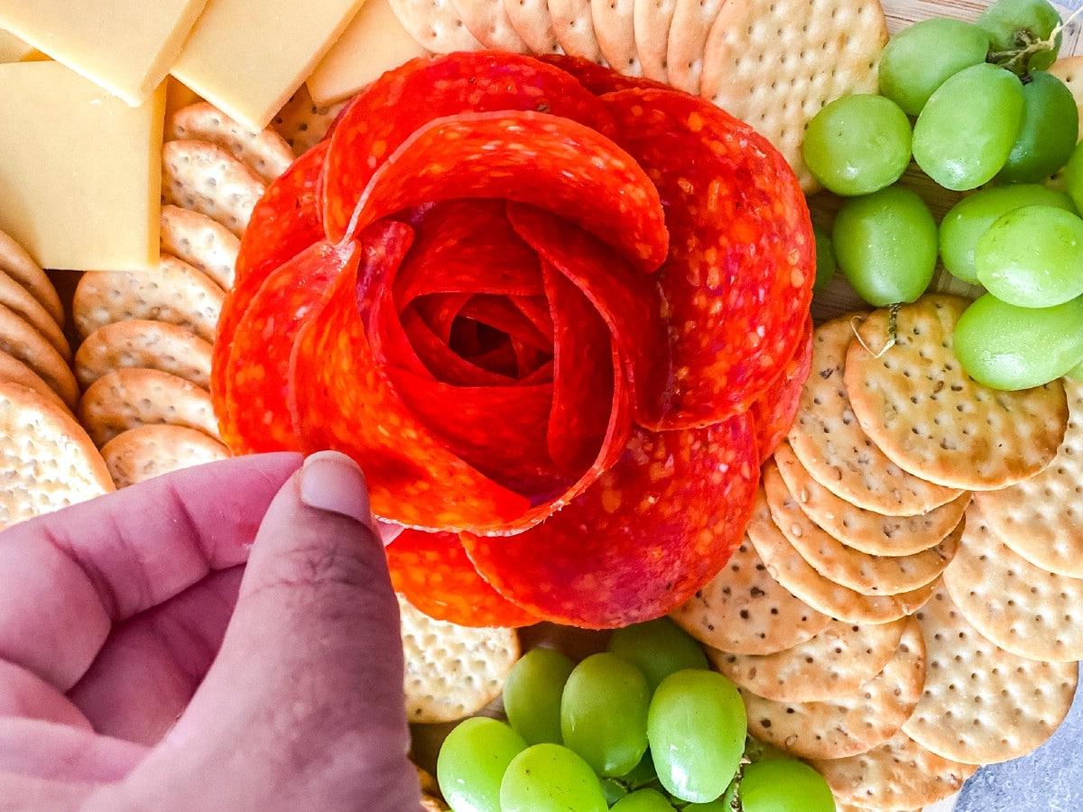 Hand touching pepperoni rose