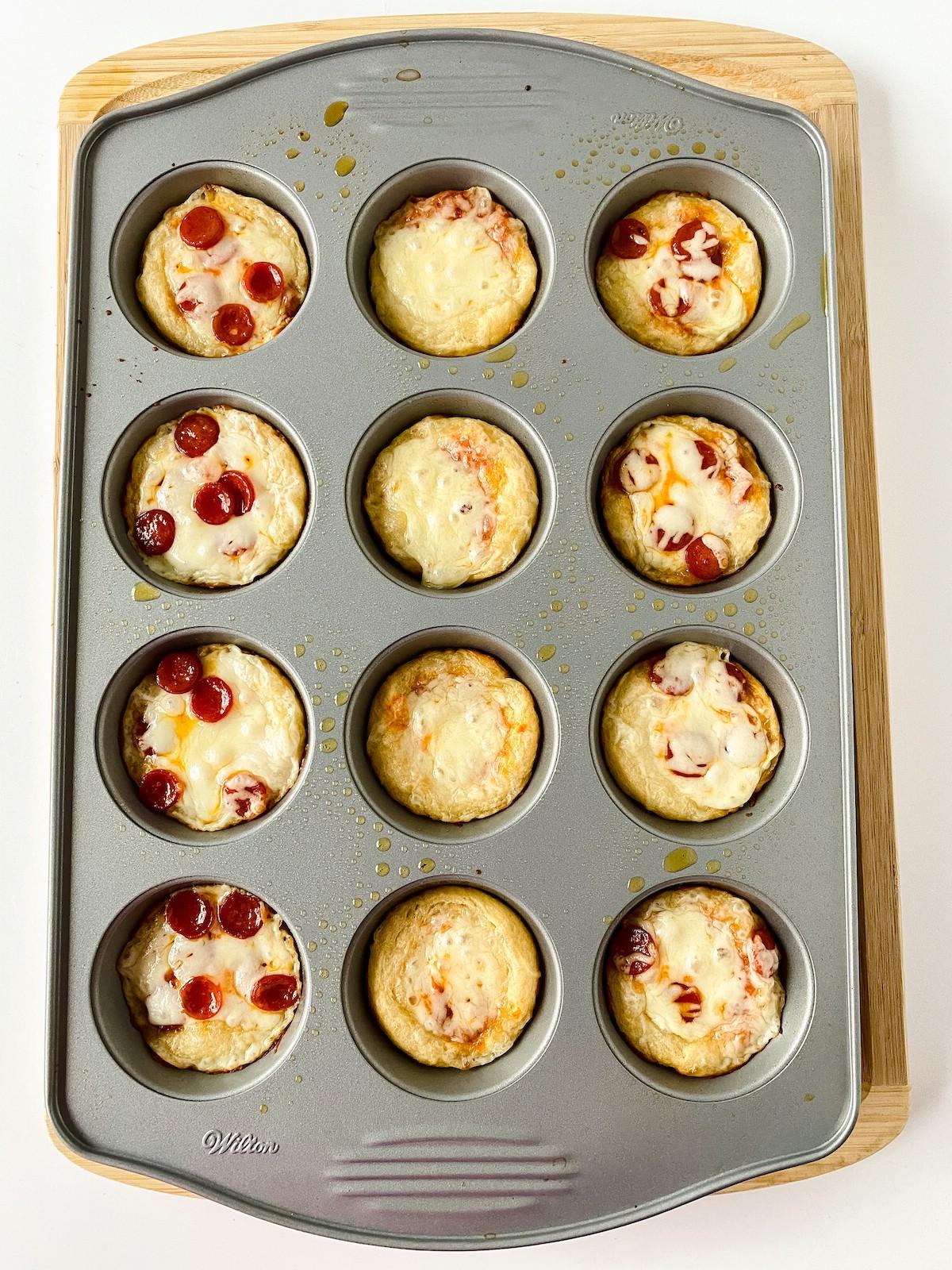 Baked mini deep dish pizzas still in muffin pan